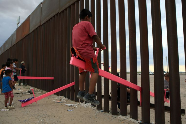 Mexicaanse en Amerikaanse families spelen op vermoedelijk 's werelds enige transnationale wipwap, op de grens tussen Mexico en de VS bij Ciudad Juarez. Het speelgoed is een idee van architect Ronald Rael, die met dit en andere ontwerpen aandacht vraagt voor de problematiek rondom vluchtelingen en barrières.  Beeld AFP