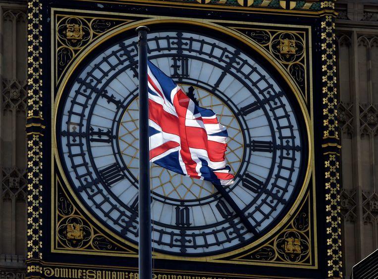 De vlag van het Verenigd Koninkrijk waait in de wind voor de Big Ben in Londen.  Beeld REUTERS