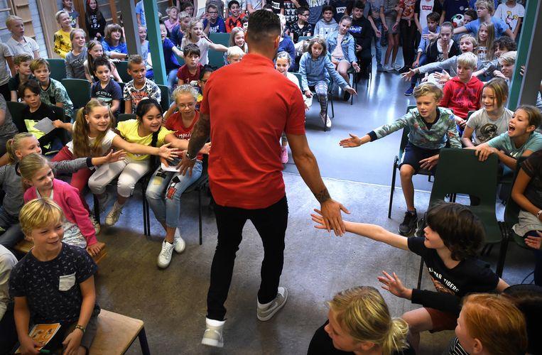 Mathias Bossaerts, de Belgische verdediger die NEC heeft gestrikt, krijgt een glorieus onthaal in de aula van de Nijmeegse basisschool NSV2. Beeld Marcel van den Bergh/de Volkskrant