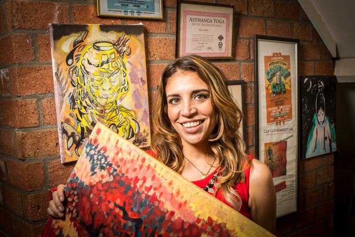 Aliana Almao toont de schilderijen die ze thuis,  op zolder, schilderde.