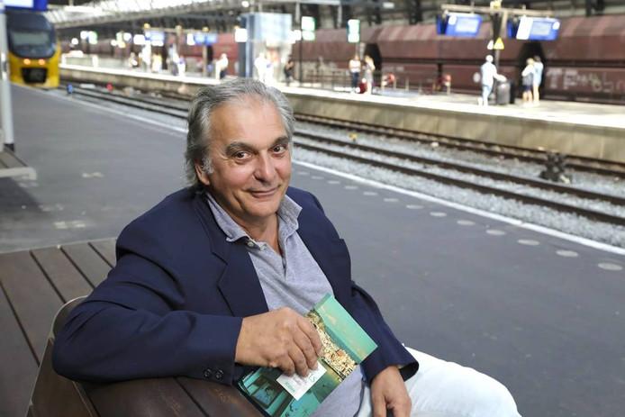 Gert Hage met zijn boek op het station van Amsterdam. Binnenkort gaat hij weer voor twee maanden terug naar Napels. Foto Marco Keyzer