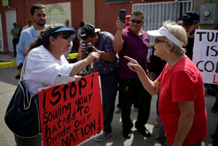 A pro-Trump demonstrator en een anti-Trump-demonstrant buiten het ziekenhuis in El Paso waar de Amerikaanse president een ontmoeting had met hulpverleners in El Paso.  Beeld REUTERS