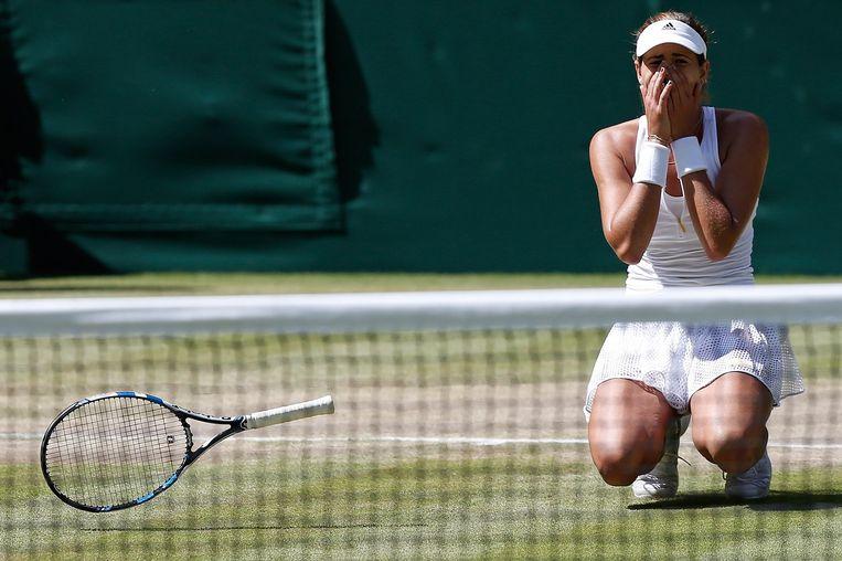 Garbine Muguruz valt op haar knieën na haar winst in de halve finale. Beeld afp