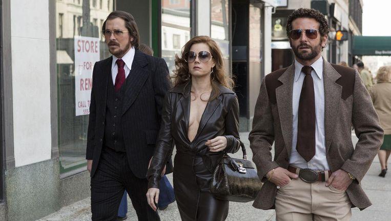 Christian Bale (l), Amy Adams (m) en Bradley Cooper (r) in American Hustle Beeld