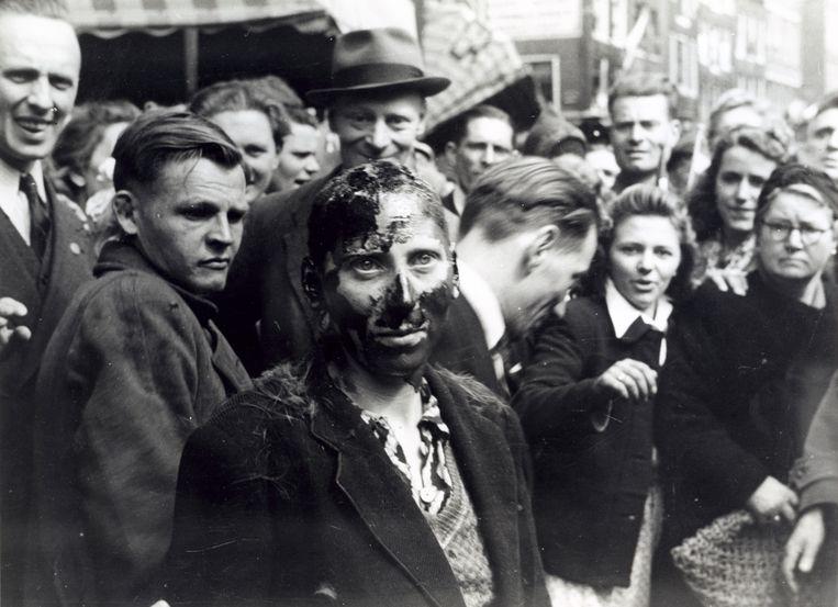 Amsterdam, 8 mei 1945: een met pek ingesmeerde 'moffenmeid' wordt uitgejouwd door een groep omstanders.   Beeld Hollandse Hoogte / Spaarnestad Photo