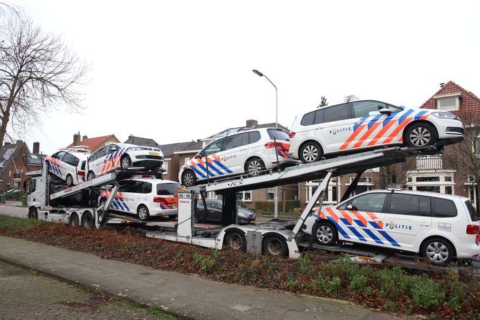 Politiewagens worden van een trailer geladen bij het politiebureau in Tiel. De extra wagens worden ingezet tijdens de jaarwisseling.