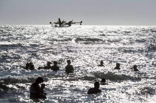 Een blusvliegtuig haalt voor de Italiaanse kust bluswater uit de zee.