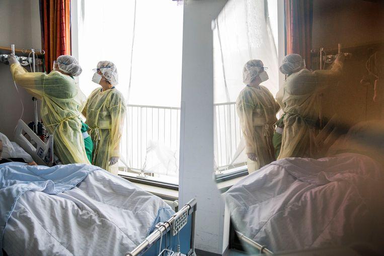 Artsen en verpleegkundige in beschermende pakken op de afdeling waar corona patiënten liggen in het Ikazia ziekenhuis, Rotterdam. Beeld Arie Kievit