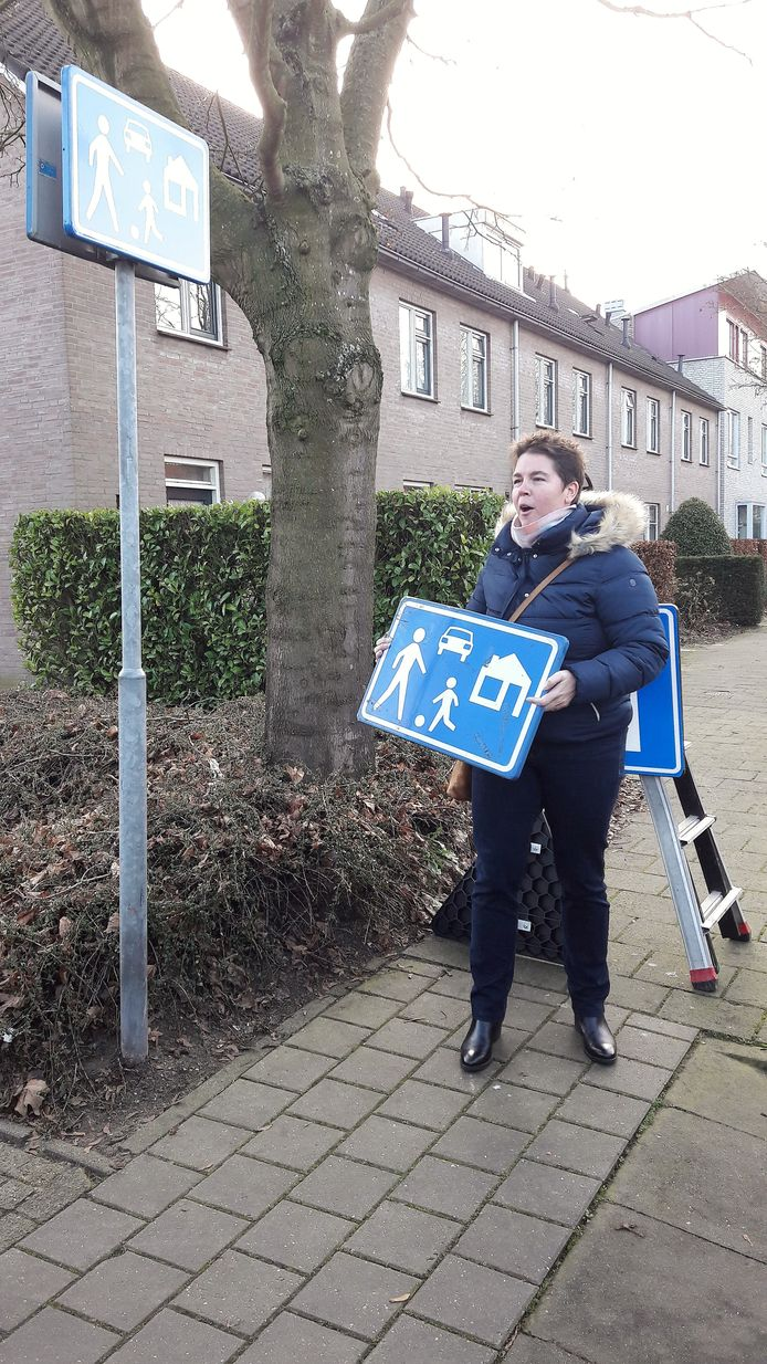 De Roosendaalse wethouder Inge Raaijmakers houdt het oude, aluminium bord vast. Het nieuwe 'refurbished sign' hangt aan de paal.