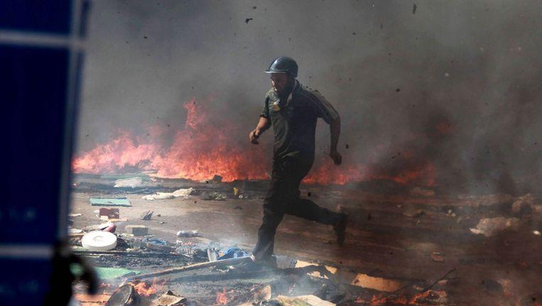 Een demonstrant rent door rookwolken en traangaswolken in Caïro, vlakbij de Rabaa Adawiya-moskee. Beeld epa