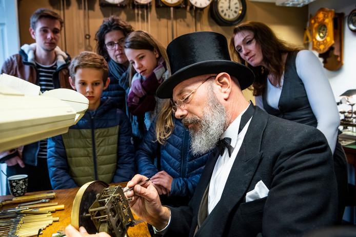 Klokkenmaker Ronald Lemmers geeft tijdens de studioroute uitleg over de werking van een oude klok.