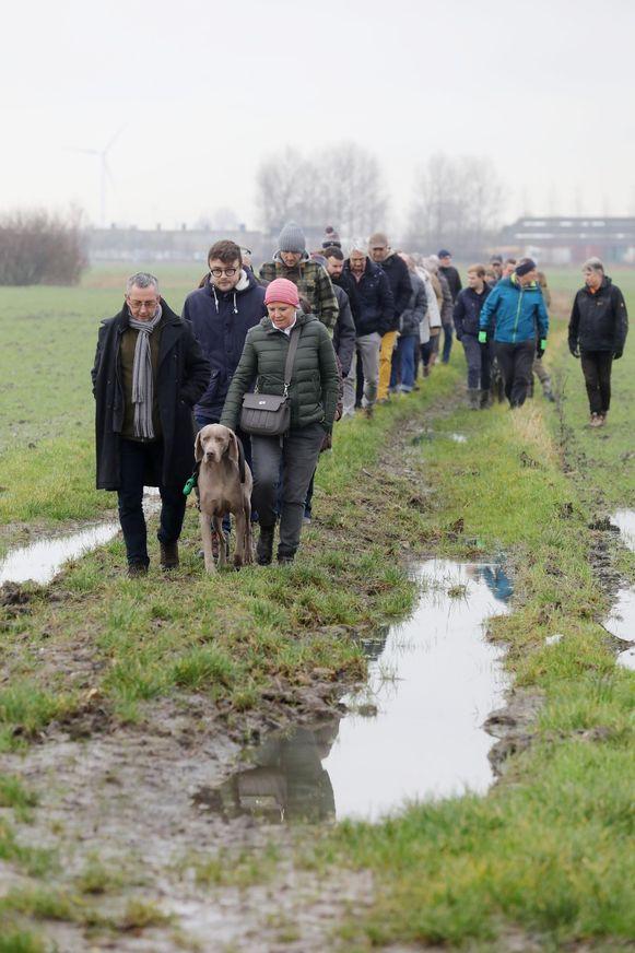 De buurtbewoners wandelen de verbindingsweg door de velden in.