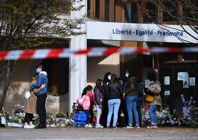 Mensen leggen bloemen voor het Collège du Bois d'Aulne in Conflans, de middelbare school waar Samuel Paty lesgaf.  Beeld AFP