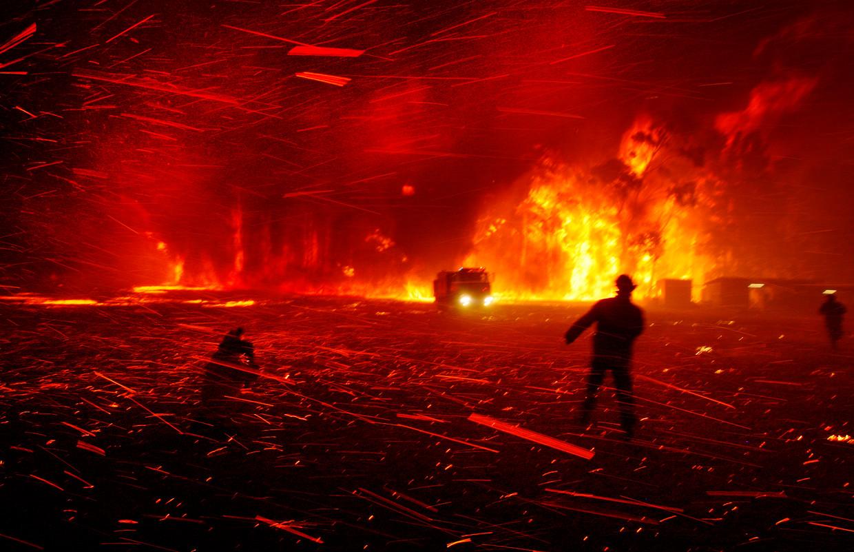 Brandweerlieden proberen bij Orangeville, ten westen van Sydney, een bosbrand te blussen wanneer een explosie een enorme vonkenregen veroorzaakt.