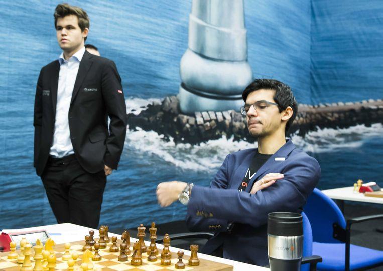 Anish Giri denkt na over zijn volgende zet terwijl Magnus Carlsen zijn beurt afwacht. Beeld EPA