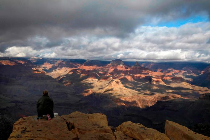 Een vrouw zit dichtbij de rand van een klif aan de zuidkant van de Grand Canyon.