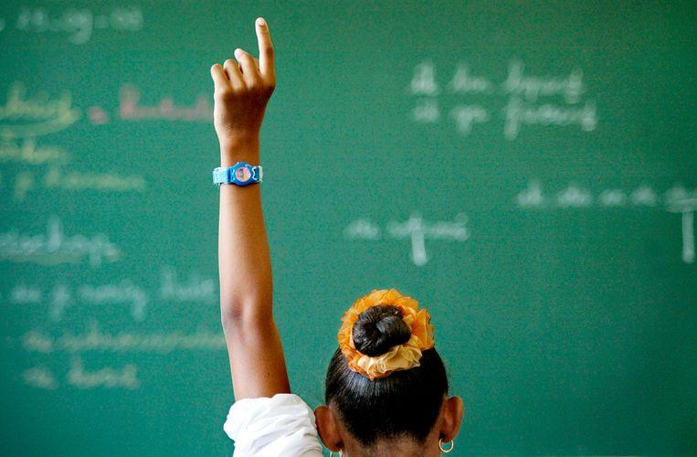 Meisje steekt vinger omhoog tijdens les in klas. Beeld Hollandse Hoogte