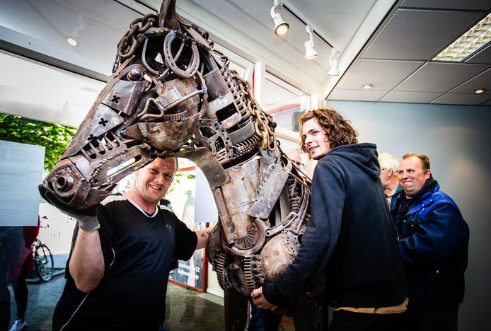 Thomas Provoost (midden) zet met wat vrijwilligers zijn paard van restmetaal in de galerij van Jaap Reedijk.