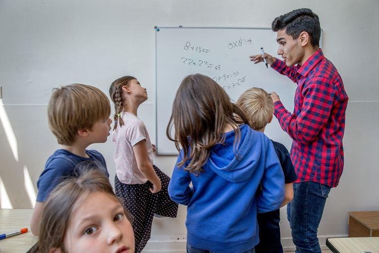 Het project 'leraar voor een dag': studenten van de pabo leren middelbare scholieren hoe ze les moeten geven aan jonge kinderen. Beeld Jean-Pierre Jans