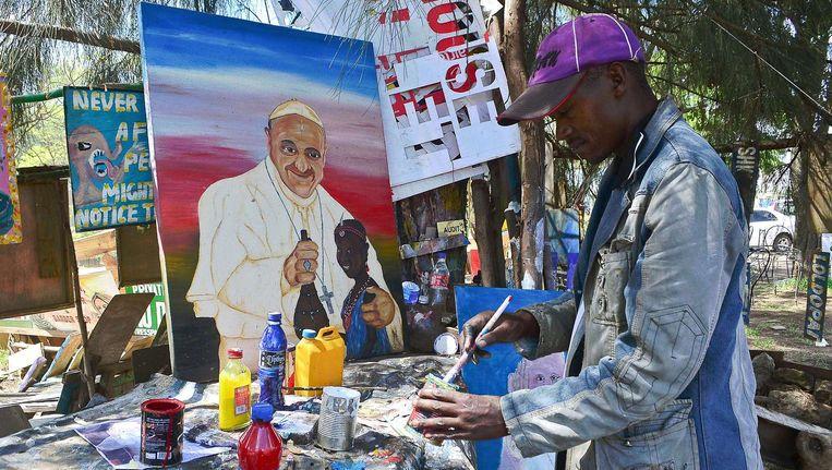 Een straatartiest in Nairobi schildert Paus Franciscus. Beeld afp