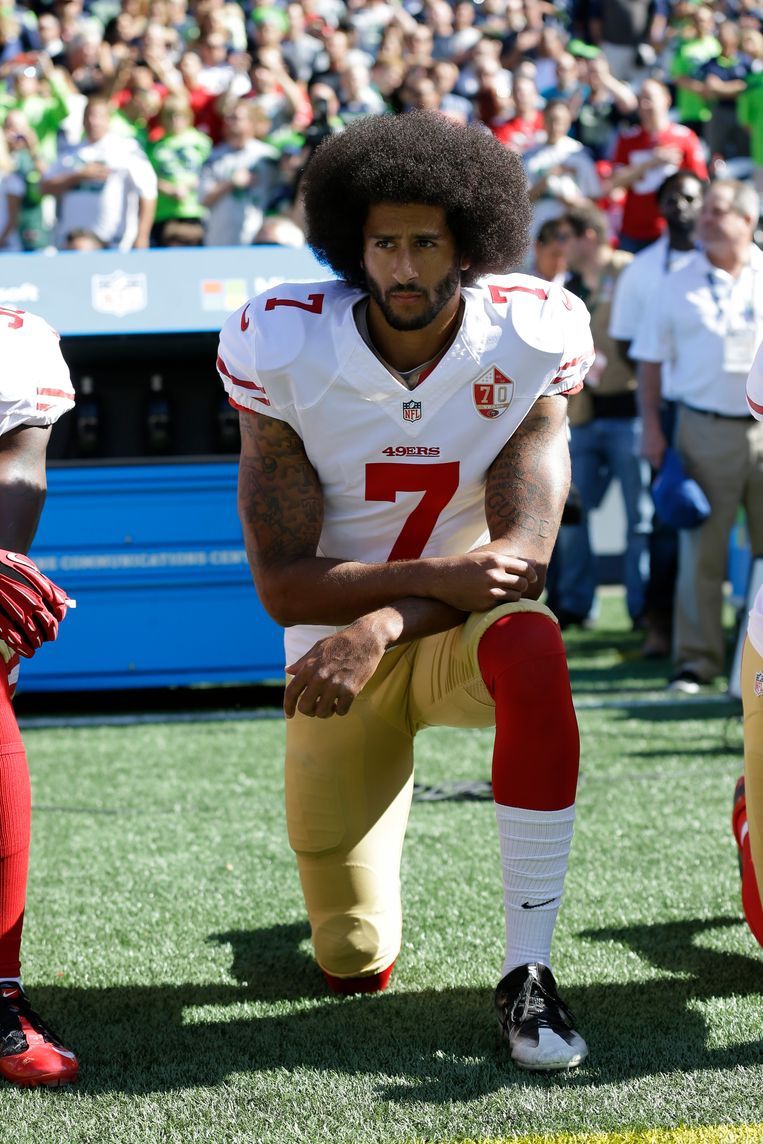 De Amerikaanse footballspeler Colin Kaepernic knielt tijdens het Amerikaanse volkslied. Beeld AP