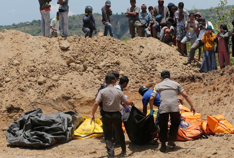 Archieffoto. Slachtoffers van de aardbeving en daaropvolgende tsunami worden in een massagraf begraven.