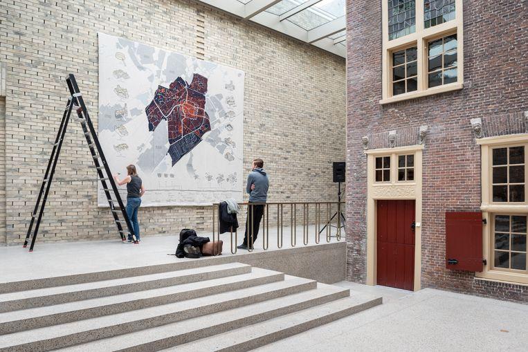 Een kaart van de stad Leiden wordt opgehangen in Museum de Lakenhal.  Beeld Simon Lenskens