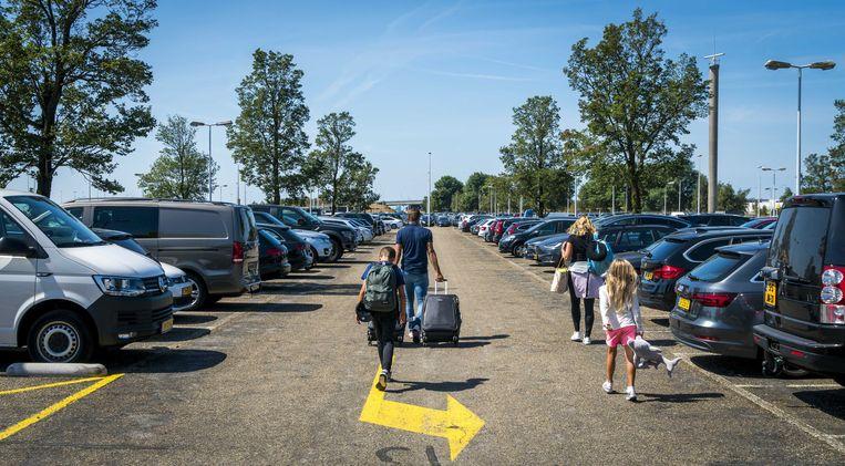 Reizigers op een parkeerplaats bij Schiphol. Beeld anp