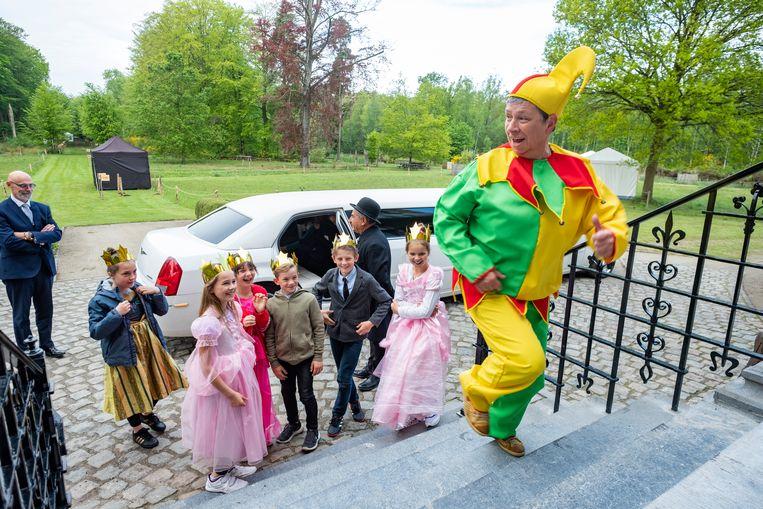 De nar begeleidt de kinderen naar het kasteel