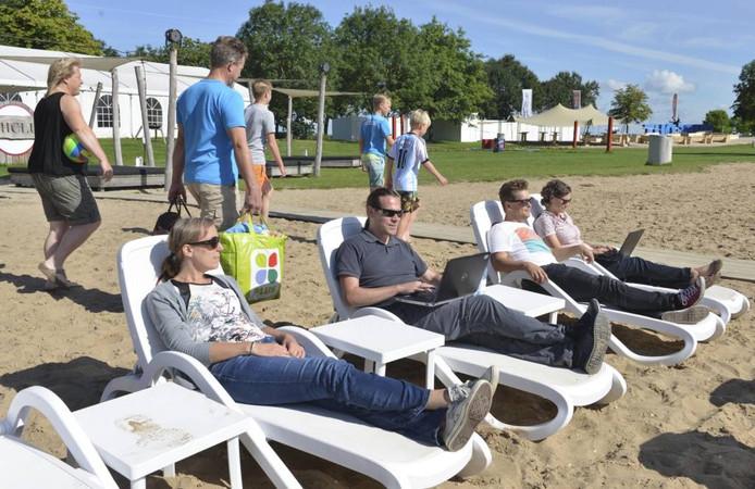 Rinke den Os (tweede van rechts) in de zon op Beldert Beach, de de tijdelijke werkomgeving van redactie Rivierenland.