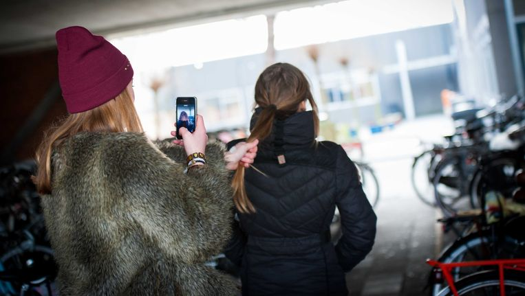 Een scholiere pest een schoolgenootje en filmt dit met een smartphone. Archieffoto Beeld ANP XTRA