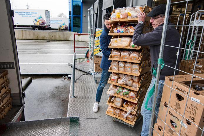 Vrijwilligers van de voedselbank laden goederen bij het distributiecentrum van AH aan de Strijkviertel.