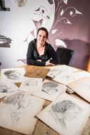 Joyce van de Wal temidden van haar gevonden portretten.