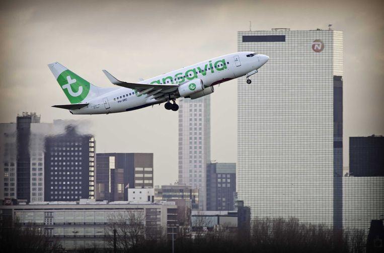 Een vliegtuig van Transavia stijgt op vanaf vliegveld Rotterdam The Hague Airport, met op de achtergrond de hoogbouw van Rotterdam.  Beeld ANP