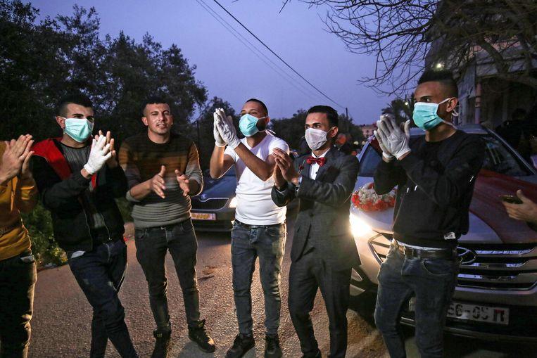 Een bruidegom en zijn familieleden in Gaza. De authoriteiten in Gama maakten op 22 maart de eerste twee besmettingen bekend in het land.  Beeld AFP