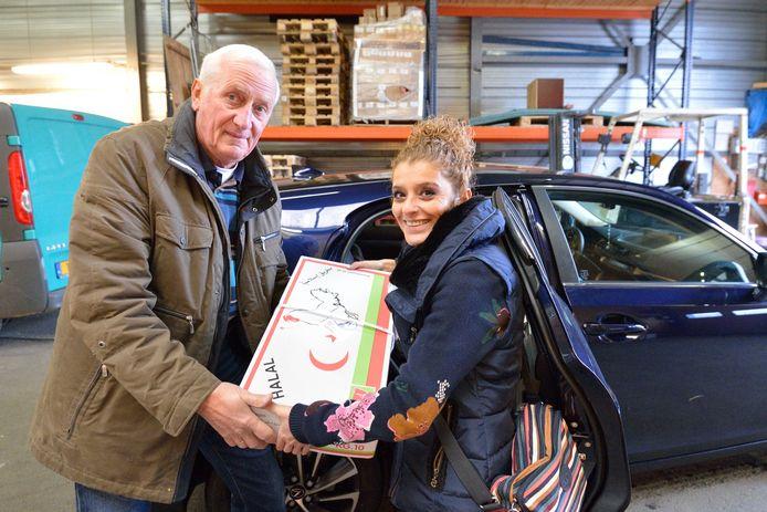 Gerrit Brinkman neemt een doos halalkip in ontvangst uit handen van Sirun Das.