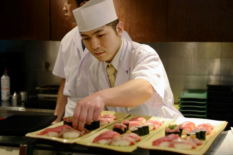 A sushi chef prepares plates of tuna sushi at a Sushi Zanmai sushi restaurant, operated by Kiyomura K.K., in Tokyo, Japan, on Monday, Jan. 5, 2015. Kiyomura purchased a 180 kilogram (397 pound) tuna for 4.51 million yen ($37,438) at the year's first auction at Tsukiji Market. Photographer: Akio Kon/Bloomberg via Getty Images Beeld null