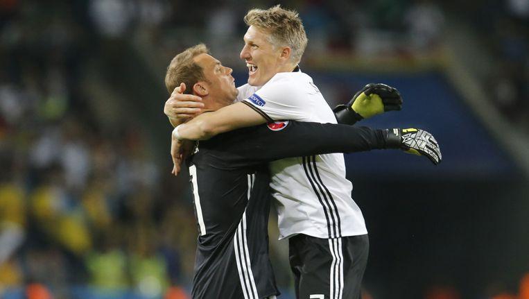 Bastian Schweinsteiger en keeper Manuel Neuer vliegen elkaar in de armen na de eerste winst op het EK. Beeld ap