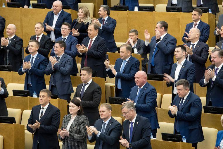 Russische parlementariërs applaudisseren nadat ze unaniem voor de grondwetswijzigingen hebben gestemd. Beeld AP