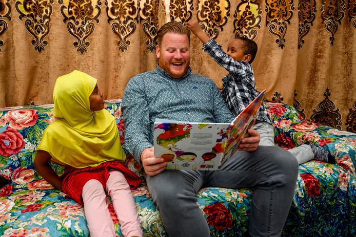 Muaad voelt aan het 'worteltjeskleur' haar van wethouder Thomas Melisse. Zijn zusje Maryama kijkt toe.