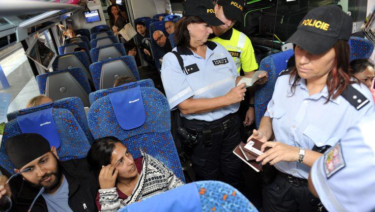 Politieagenten controleren paspoorten van treinreizigers op weg van Oostenrijk naar Tsjechië.