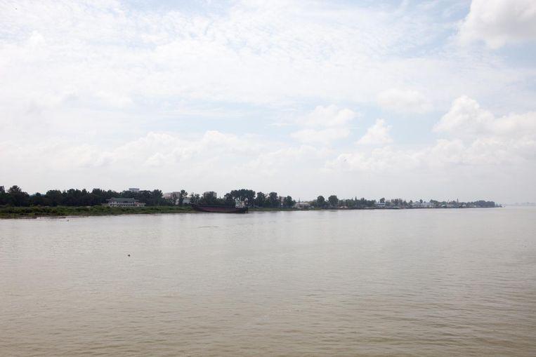 Vanaf de boot ziet de Noord-Koreaanse oever er groezelig uit Beeld Ruben Lundgren