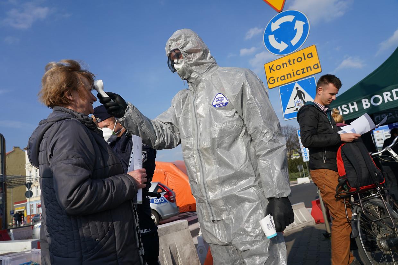 Een Poolse grensbewaker meet de lichaamstemperatuur van een vrouw die grens wil passeren. In Polen zijn er tot nu toe relatief weinig sterfgevallen pet miljoen inwoners.  Beeld Getty Images
