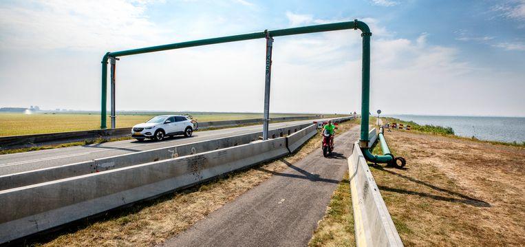 Waterpompsysteem over de dijk bij Almere om het achterliggende land van IJsselmeerwater te voorzien. Beeld  Foto Raymond Rutting / de Volkskrant