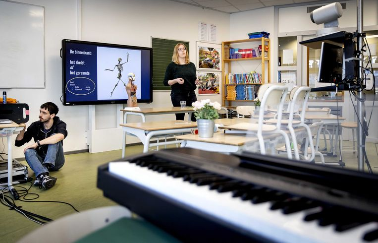 Een leraar geeft online les in een leeg klaslokaal dat is omgebouwd tot studio.  Beeld ANP