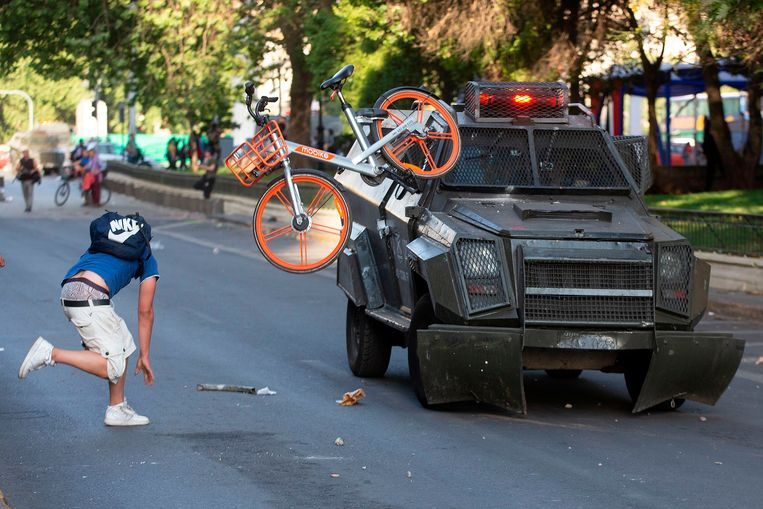 Een man gooit een fiets tegen een gepantserde politieauto in Santiago. Beeld AFP