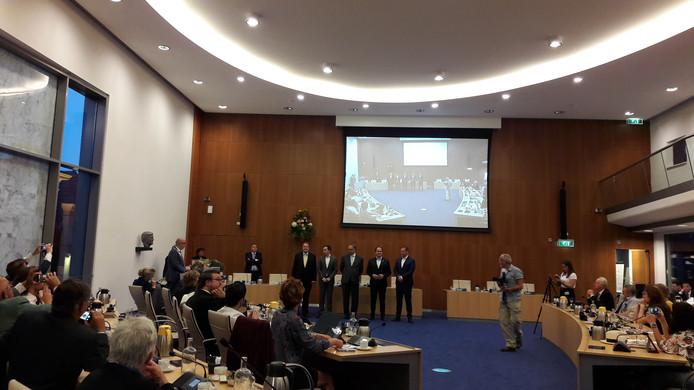 De vijf wethouders op een rij voor de benoeming van het nieuwe college. Geheel links staat burgemeester Jack Mikkers achter spreekgestoelte.