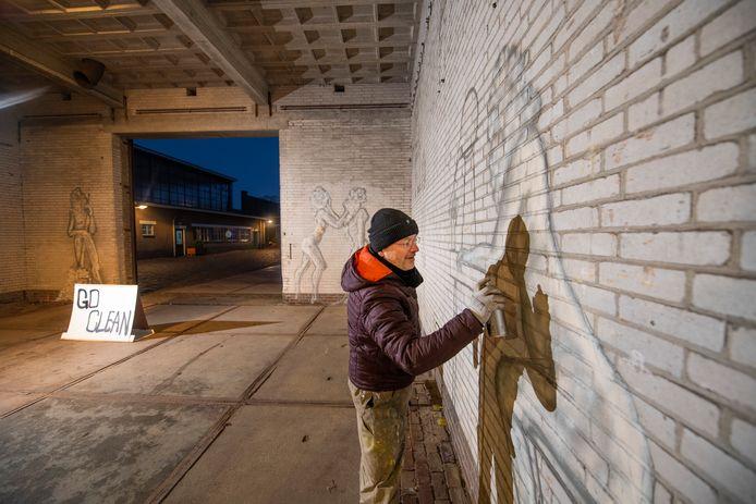 Stephan Peters werkt aan zijn muurschildering op het Zwitsal-terrein in Apeldoorn.