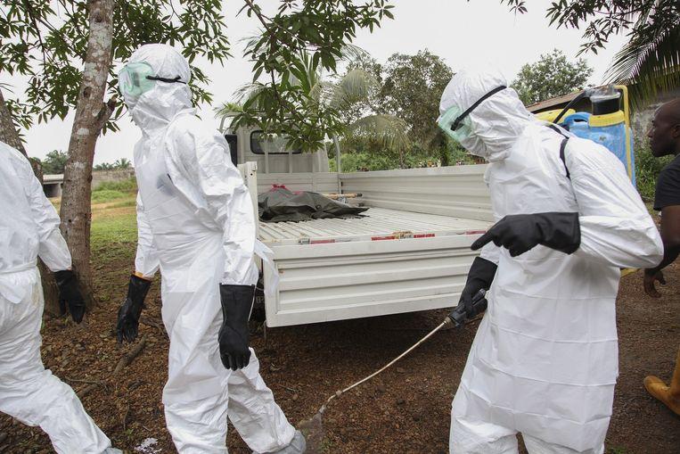 Verpleegsters in Liberia desinfecteren de omgeving van een wagen waarin het lichaam van een overleden ebolapatiënt op de laadbak ligt Beeld epa
