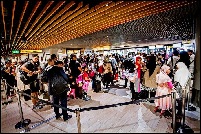 Wachtende passagiers in de rij voor de paspoort-controle van de marechaussee.